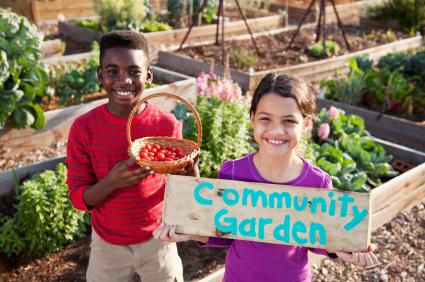 Children with 'Community Garden' sign